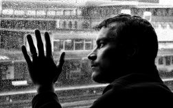 hombre solo y triste tras una ventana en un dia lluvioso